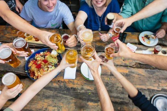 A group of people sitting around a table clinking their beer glasses together