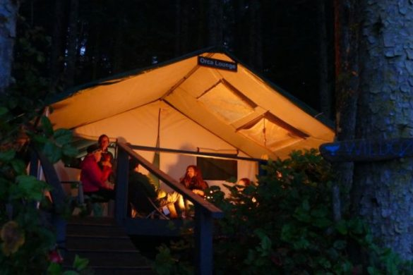 People sitting outside a tent in the evening