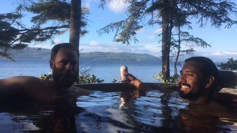 Two men sitting in a hot tub in the Canadian wilderness