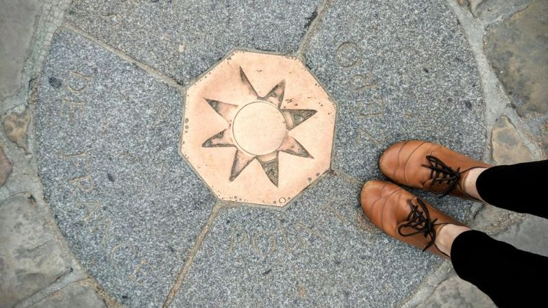 The bronze plaque at Point Zero, with a persons shoes.