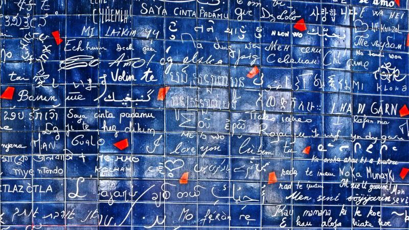 Blue tiled wall covered in graffiti