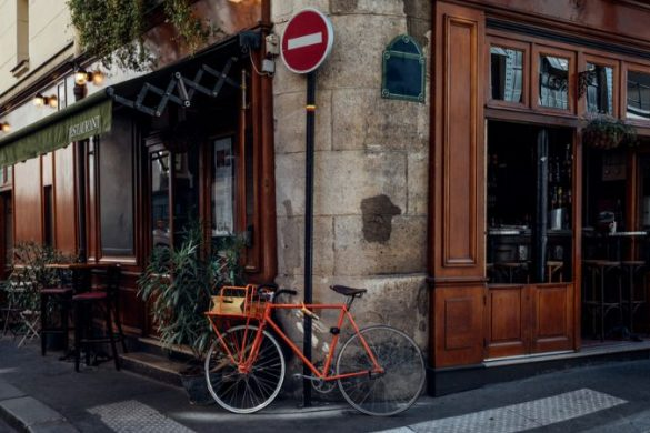 An orange bicycle parked outside a cafe in paris