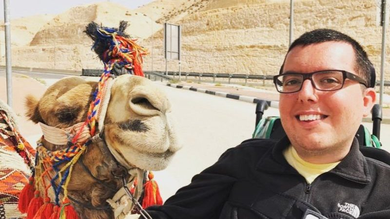 A smiling man sitting beside a camel