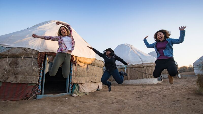 Three travellers jumping outside a yurt in Kazakhstan
