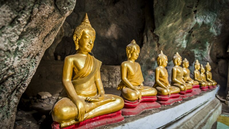 A temple filled with gold Buddhas in a cave
