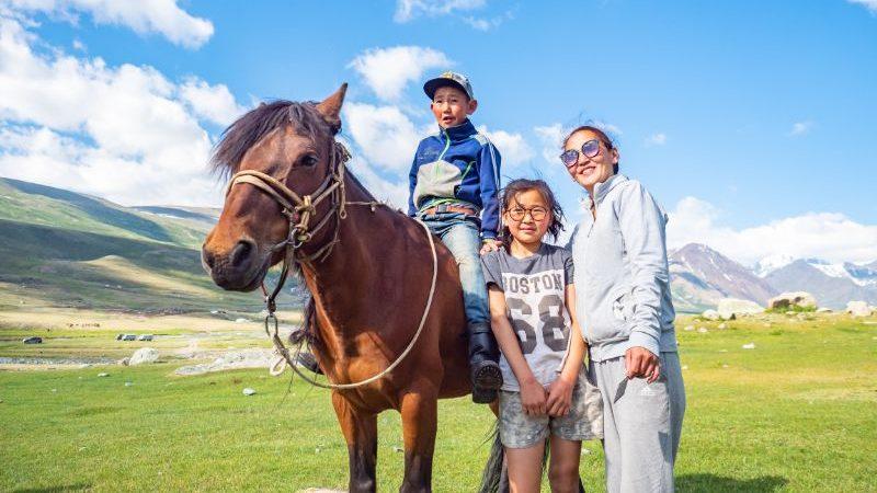 A Mongolian family stand alongside a horse