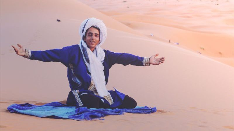A Berber wearing blue sitting on the sand in the desert