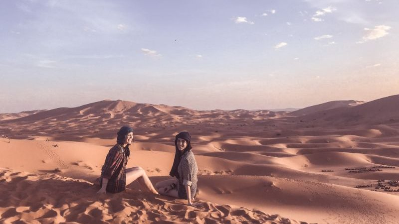 Two girls sitting on a sand dune in Morocco