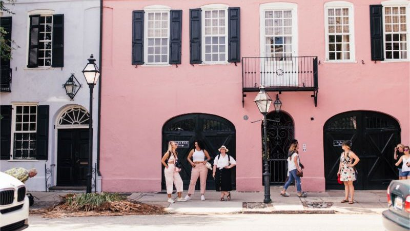 A group of travellers posing outside a pink house