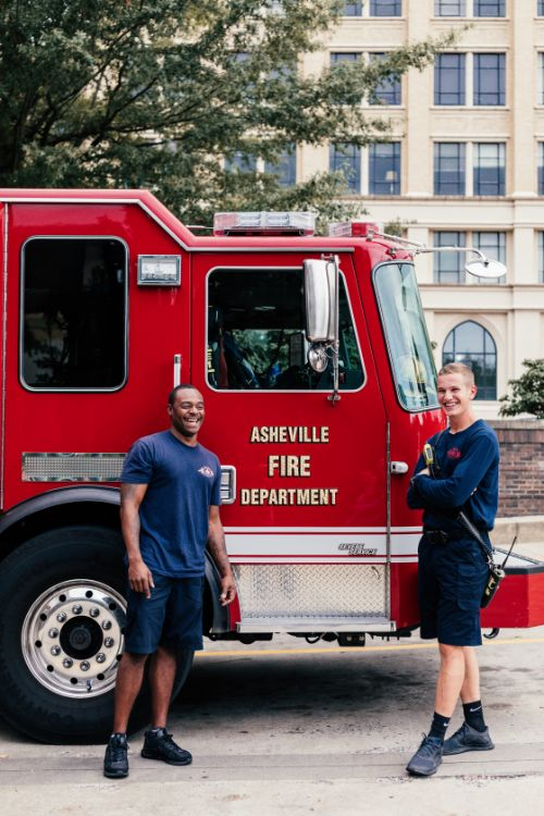 Two firefighters posing alongside their truck