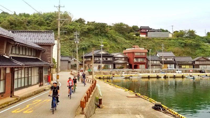 A group of cyclists riding through Togi, Japan