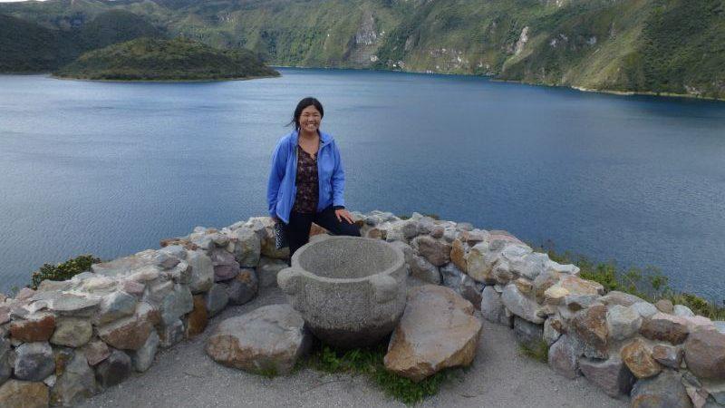 A woman standing at Cuiocha Lake in Ecuador