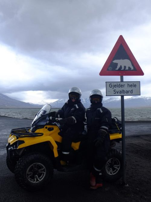 Two people on an ATV in front on a polar bear sign
