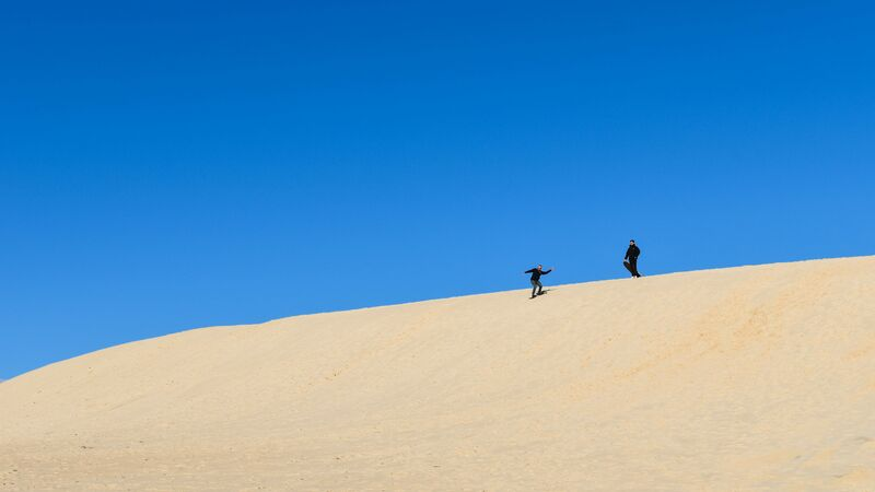 Two people sandboarding down a sanddune at Little Sahara on Kangaroo Island