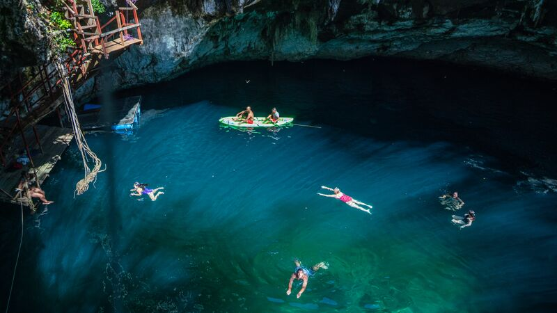 Swimmers and kayakers in a cenote in Mexico