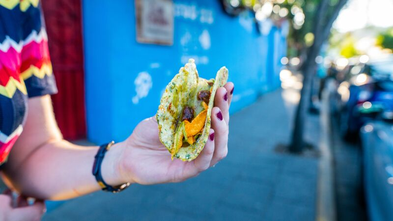 A woman holding a taco in front of a blue wall in Mexico