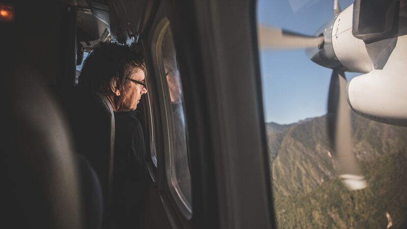 A man looking out the window of a small plane in Nepal