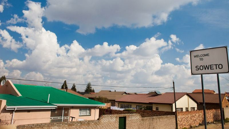 Low houses with a sign saying Welcome to Soweto.