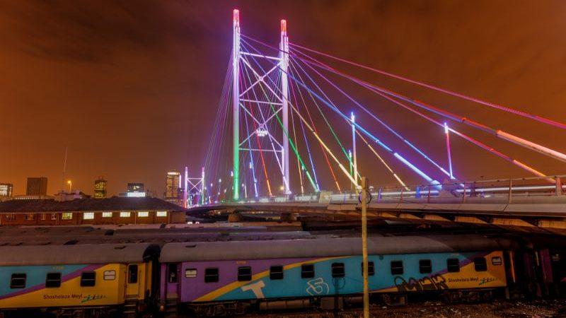 Brightly coloured bridge at night.