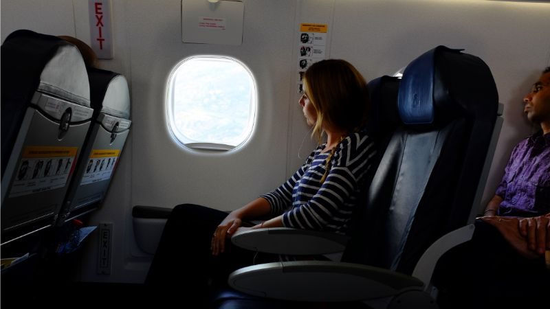 A woman looking out the window of a plane