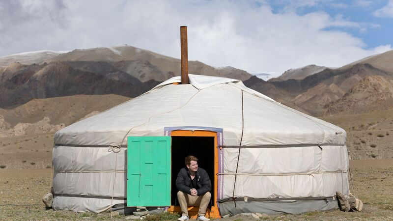 A man sitting in the doorway of a ger in Mongolia