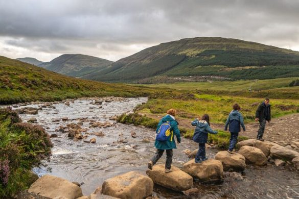 Four trekkers skip across a river in Scotland
