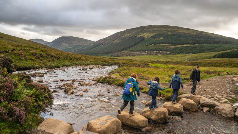 Four trekkers skip across a river in Scotland