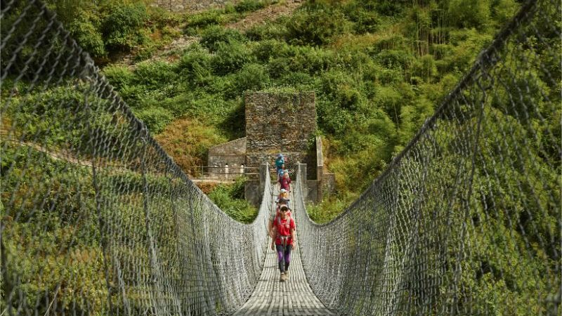 A group of trekkers crossing a suspension bridge.