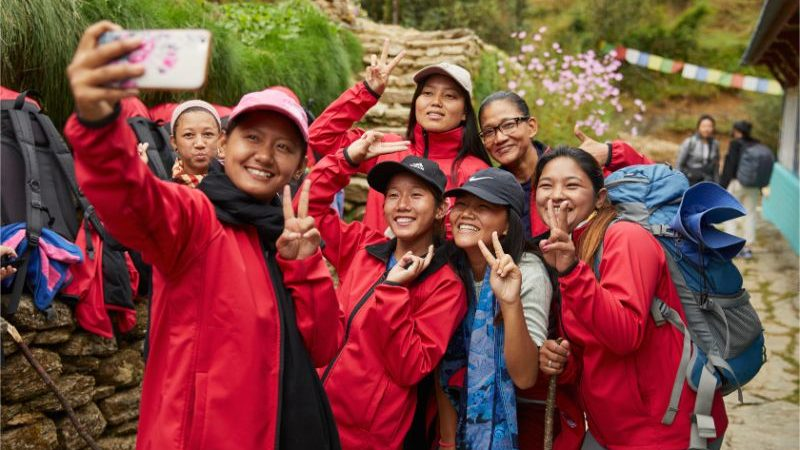 A group of porters wearing red jackets taking a selfie.