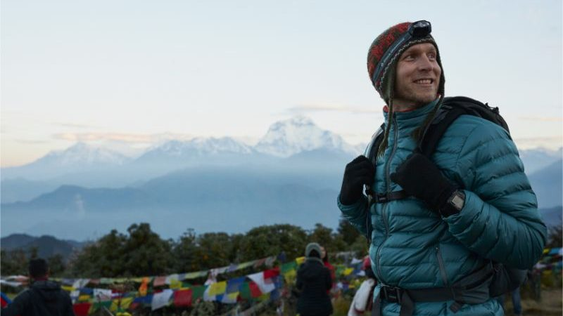 A man wearing a warm jacket, a head torch and a woolen hat in Nepal