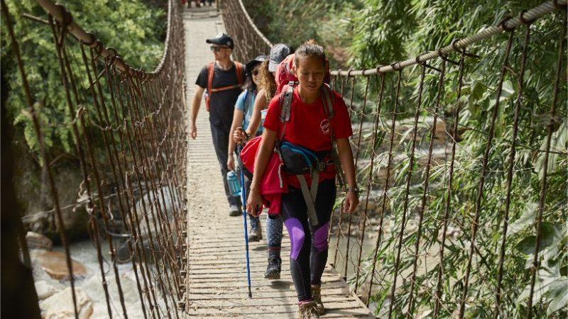 Trekkers cross a suspension bridge in Nepal