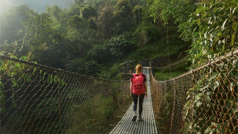 A woman with a pink backpack crosses a suspension bridge in Nepal