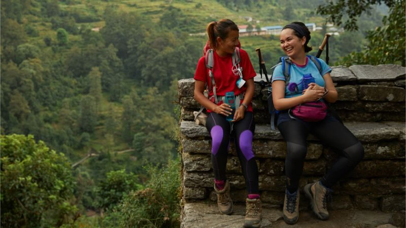 Two hikers stop for a rest on the Annapurna Base Camp trail