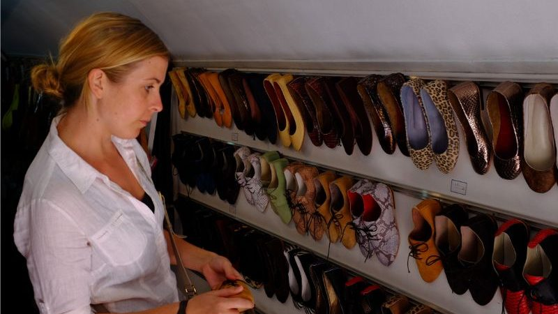 A woman looking at colourful shoes in a shop