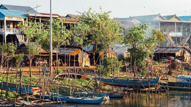 Canoes and riverside houses in Kampong Chhnang, Cambodia