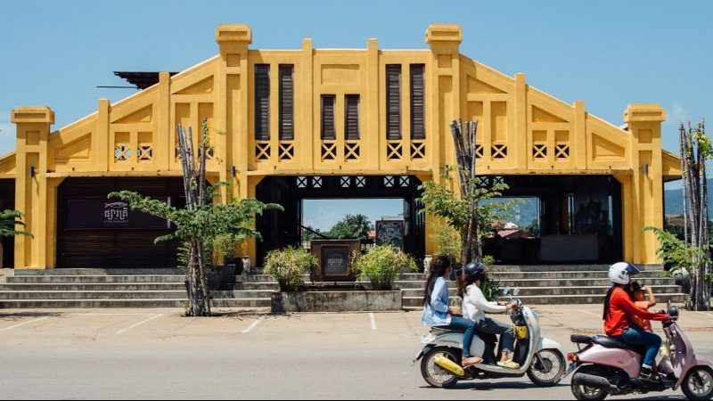 A yellow building with motorbikes riding past