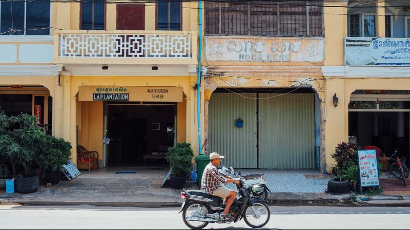 A motorbike cruises past yellow buildings in Cambodia.