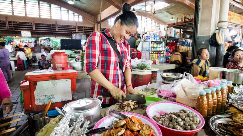 A woman preparing seafood at a market in Cambodia