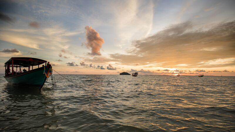 A boat and island at dusk.
