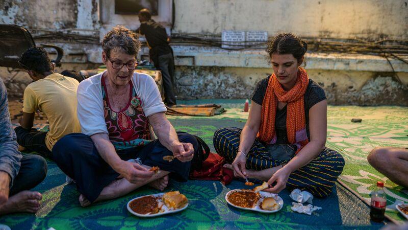 Female travellers eating on the floor in Goa