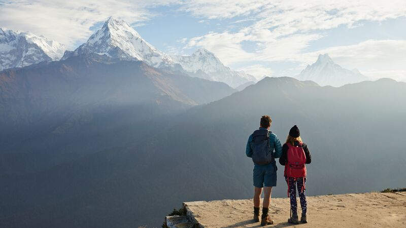 Two hikers looking at mountains in Nepal.