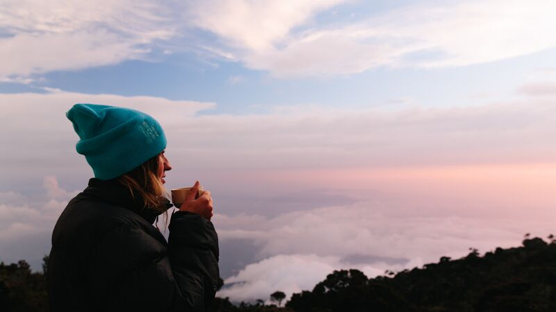 A young woman watching the sun rise at Mt Kinabalu