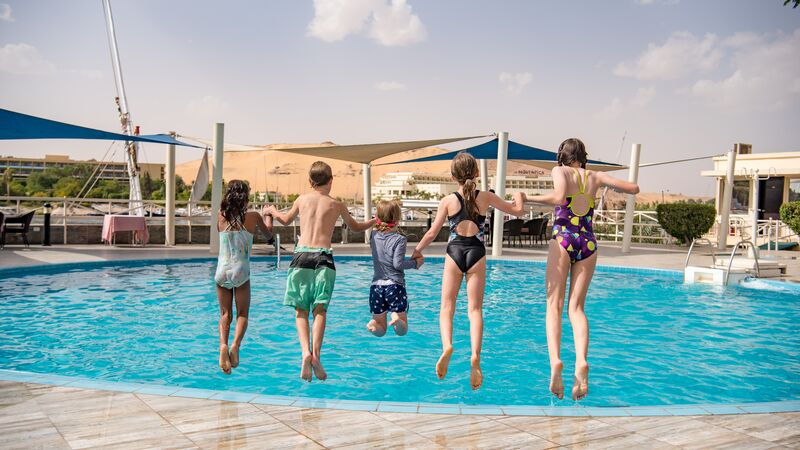 Five kids jumping into a swimming pool in Egypt