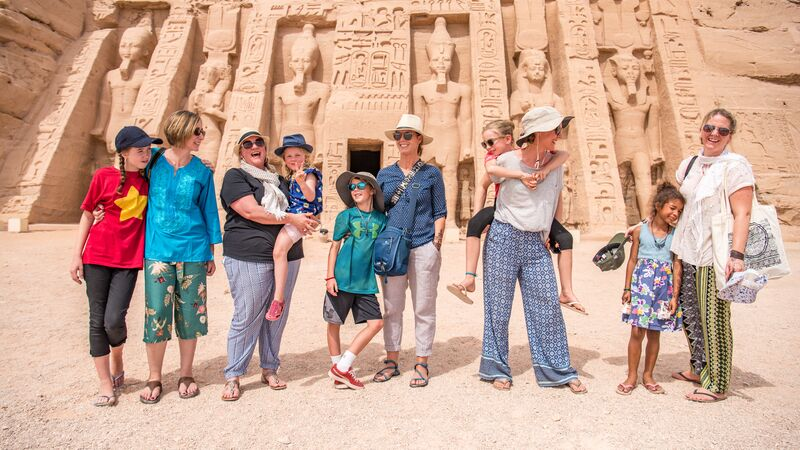 A group of travellers, including young children, at Abu Simbel temple in Egypt