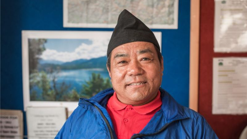 A smiling man wearing a blue top and a black Nepalese hat.