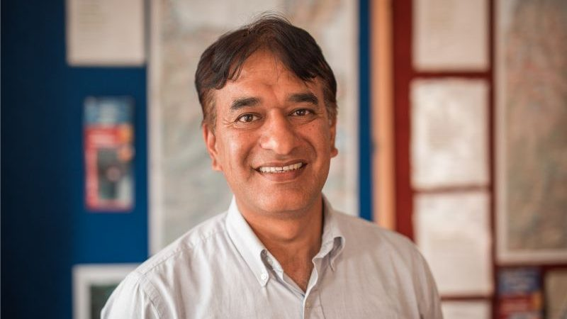 A smiling man wearing a white shirt.