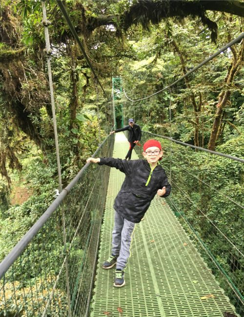 Two boys on a hanging bridge in a jungle