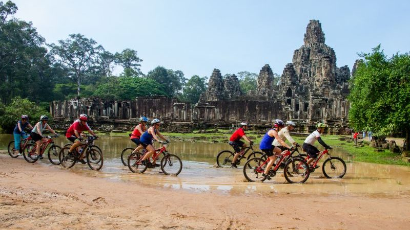 Cyclists riding through Angkor Wat, Cambodia.