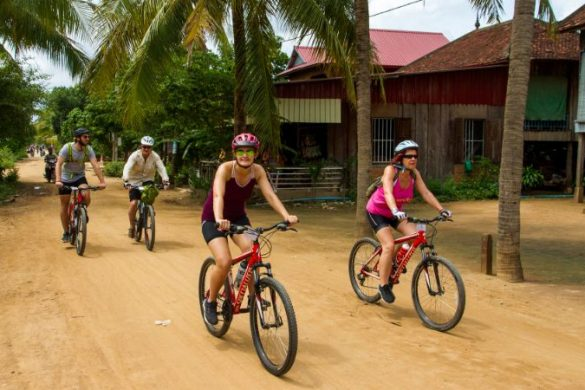 Cyclists riding through a village.