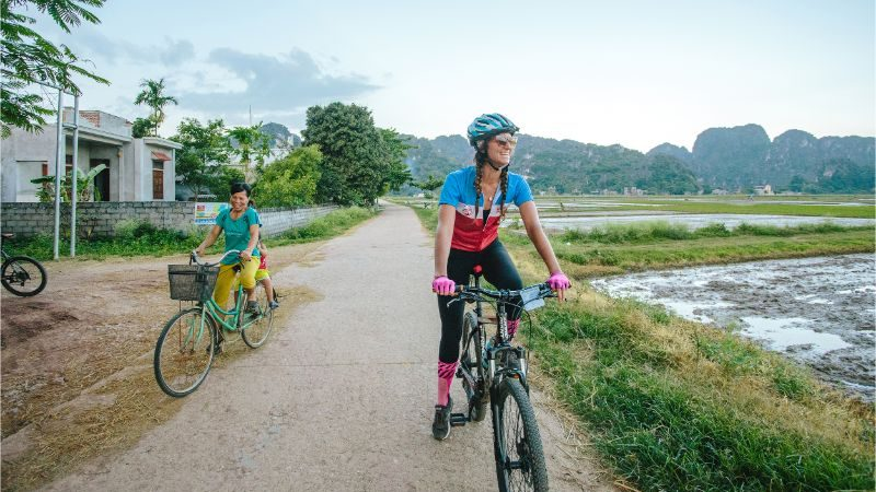 A cyclist riding past rice paddies in Vietnam
